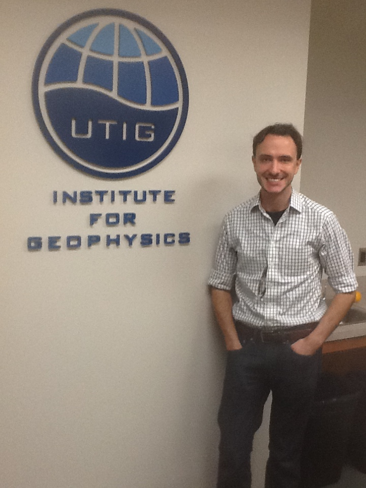 Dusty Schroeder poses by the UTIG logo