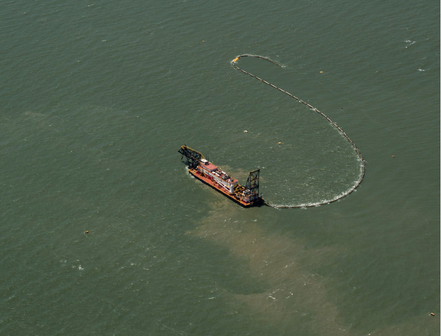 An aerial view of a dredging vessel at sea. Trails of sand are visible in vessel's wake.