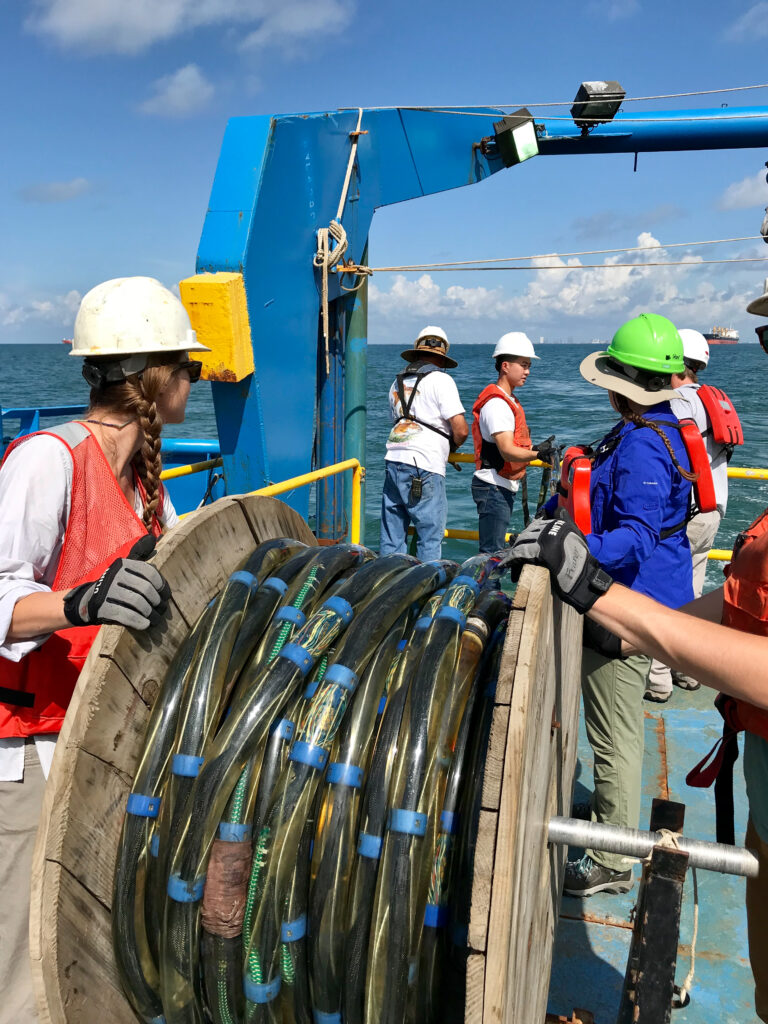Students unrolling a seismic streamer from aft of scientific research vessel during UTs Marine Geology and Geophysics field class