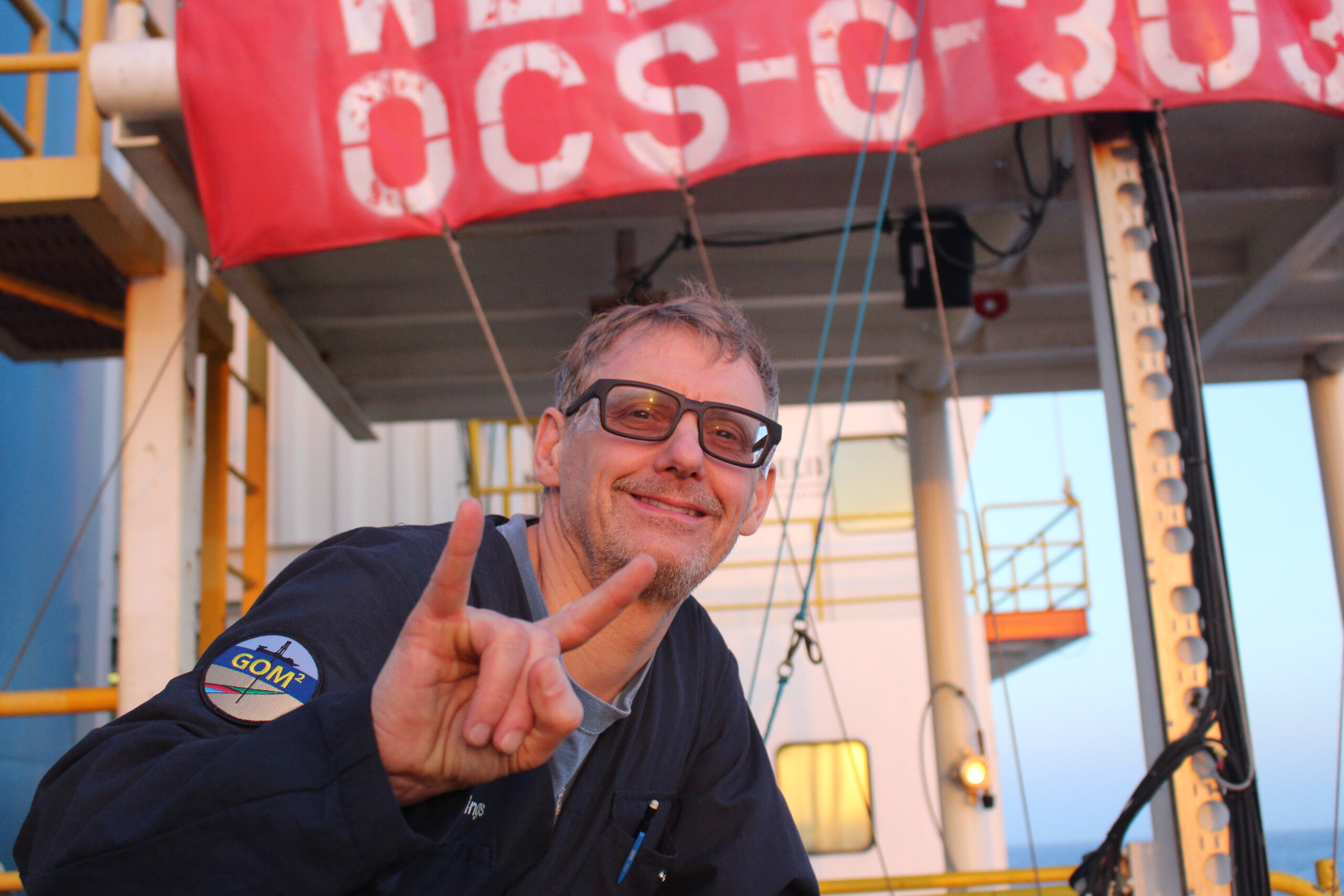 A photo of Peter Flemings with the deck of the deep-water coring vessel behind him.