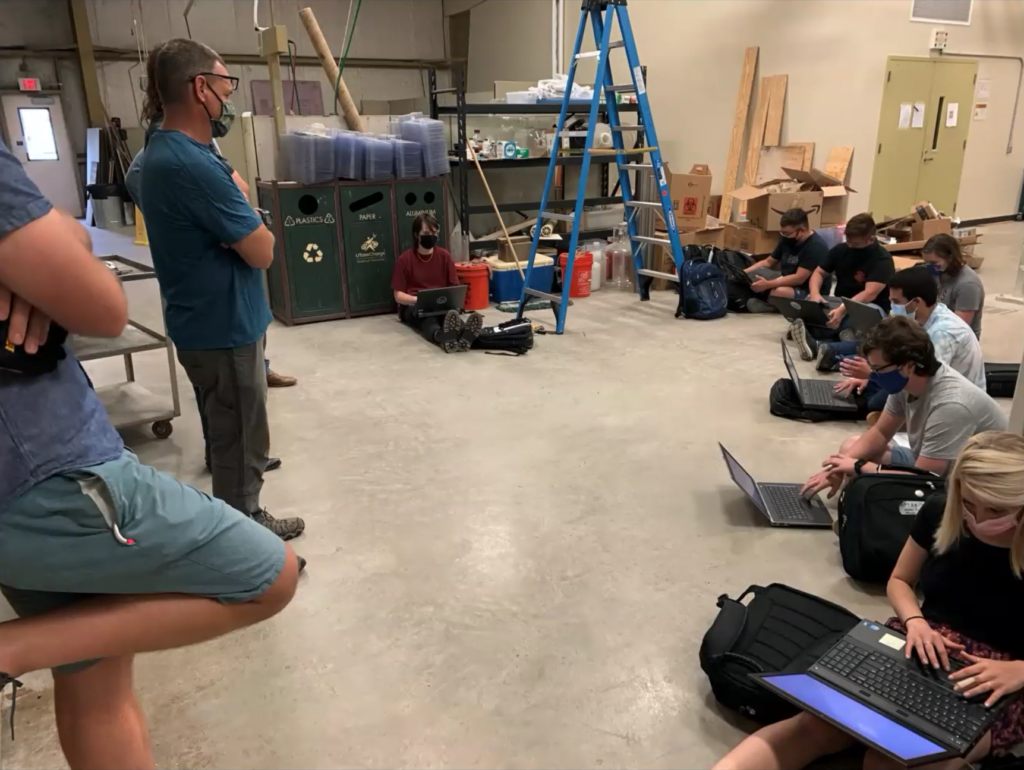Masked students sitting on the floor of a warehouse with their new laptops