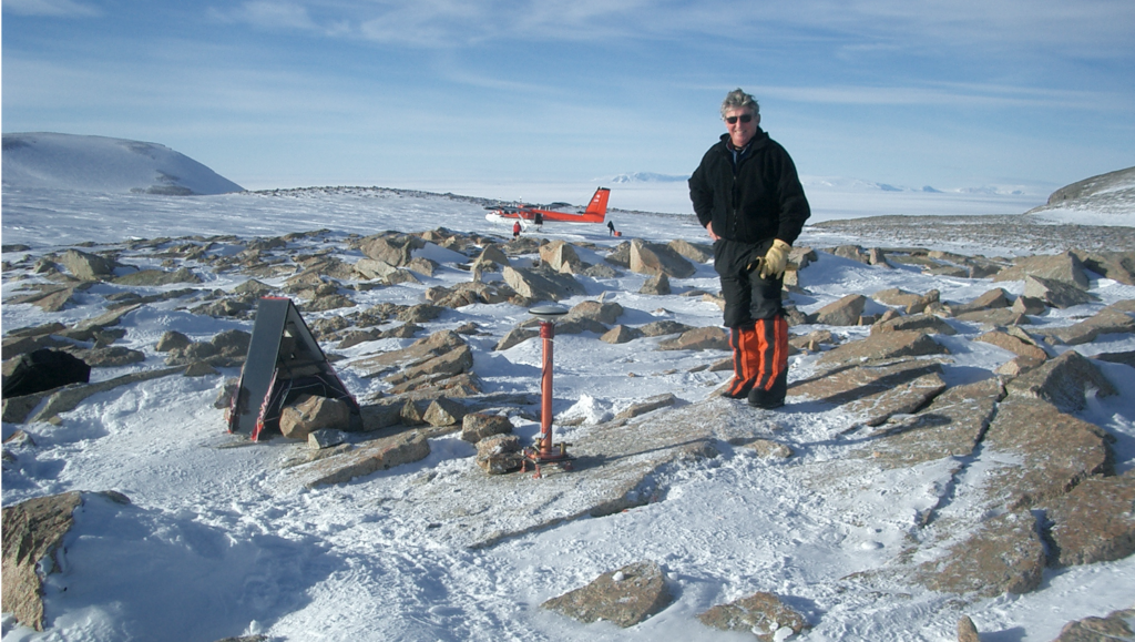 A picture showing Ian Dalziel standing among snow and rocks with a deployed sensor ahead of him. In the background is a landed Twin Otter aircraft.