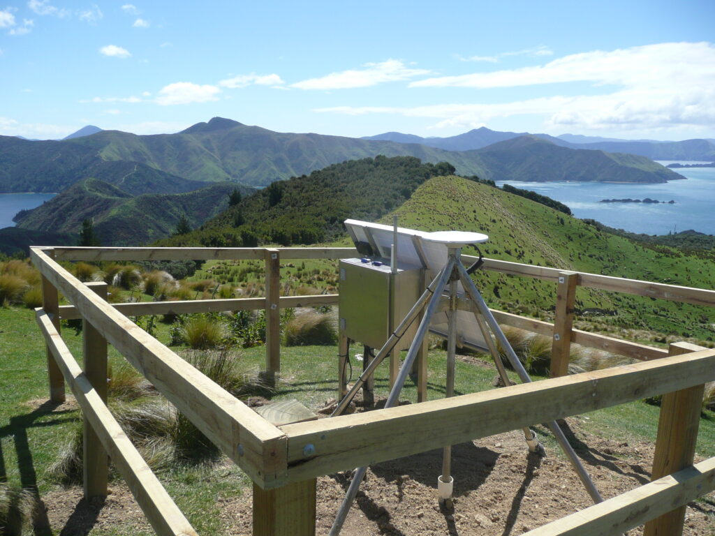 A GPS station on a hilltop overlooking mountains and water.