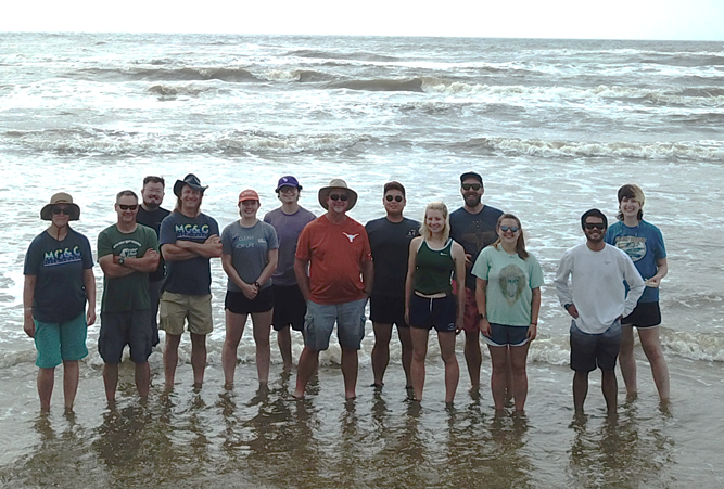The class posing for a group photo on the beach